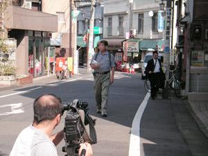 「地図を見ながら歩いてください」の指示に、中里通りを歩く中平さん。この通りは、昔ながらの風情を残すお店がたくさんありました。