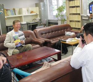 『大山北尾根・支尾根』を手に写真撮影される岡澤さん。最初は緊張気味でしたが、とても素敵な笑顔で撮影に応じられていました。ライトも点けて本格的な撮影でした。