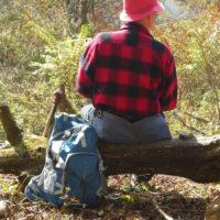 倒木に腰掛けて休憩する岩田さん