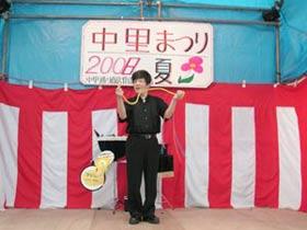 「ひも」のマジックを披露する佐久間さん。後ろの「中里まつり 2008夏」の看板の「8」の文字が若干気になります。